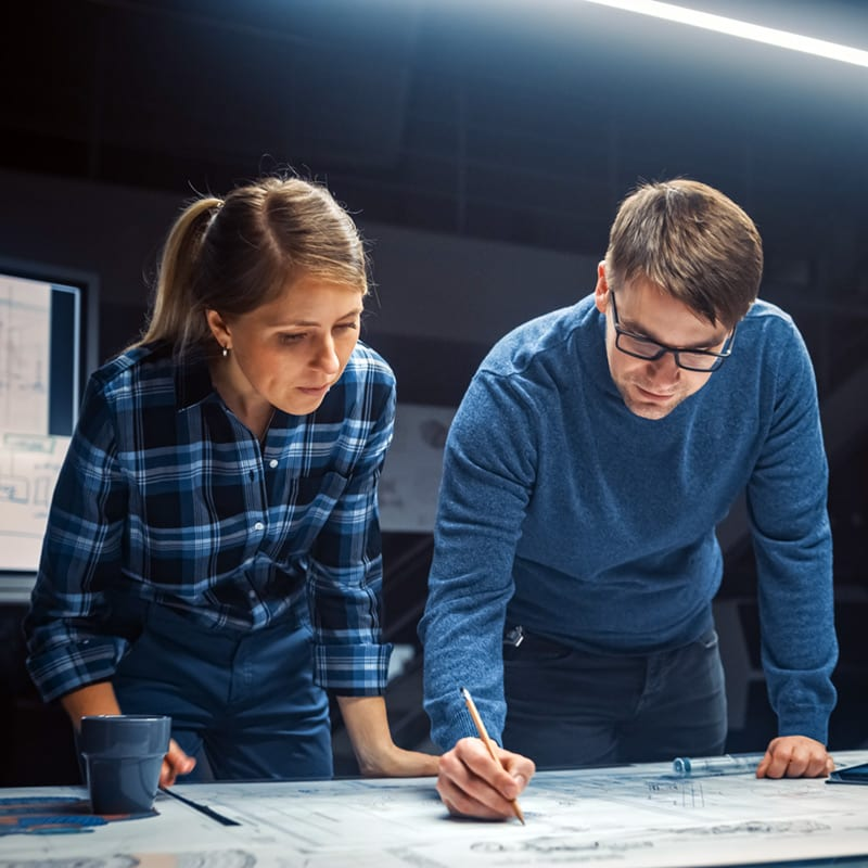 A woman and man work on a Facilities Engineering Project as part of their Engineering Management degree from NC State University