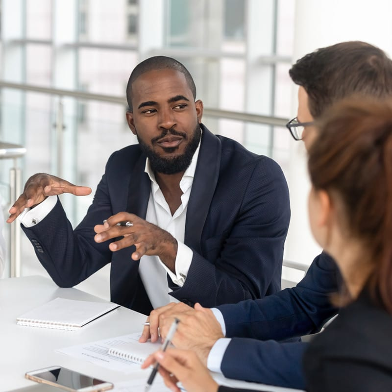 A man leading an engineering team meeting after receiving his Master of Engineering Management degree from NC State University